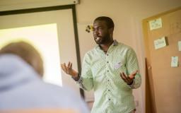 Mann mit Migrationshintergrund spricht als Seminarleiter vor einer Gruppe