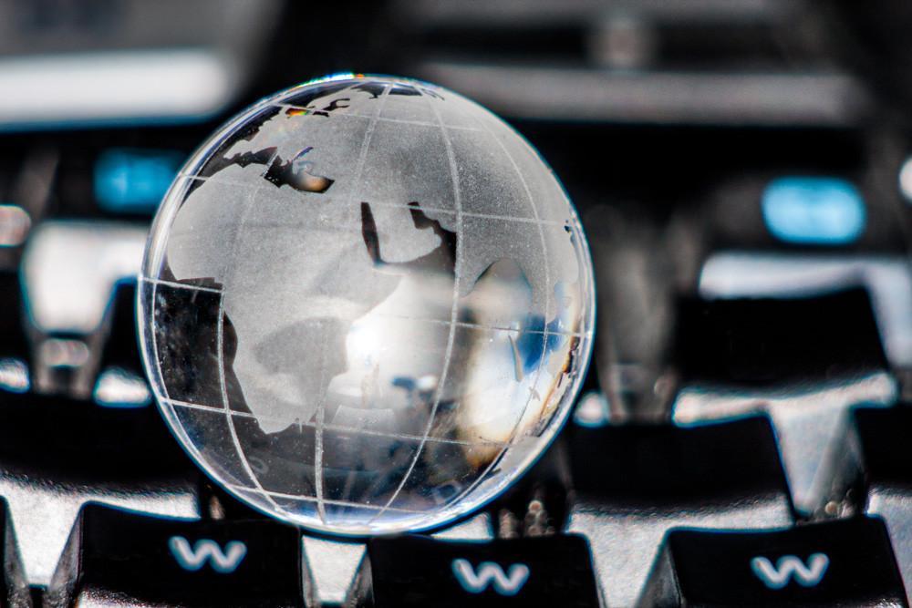 Weltkugel auf einer Tastatur // Foto: Thorben Wengert / pixelio.de